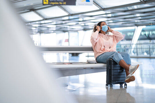 Young woman listening to music while wearing protective face mask sitting at airport