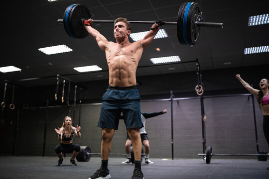 Amputee athlete picking barbell with people cheering in background at gym
