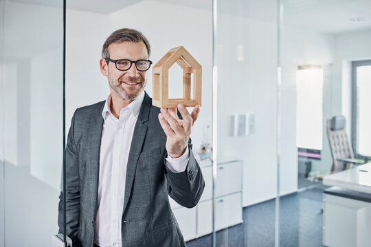 Smiling businessman looking at architectural model in office
