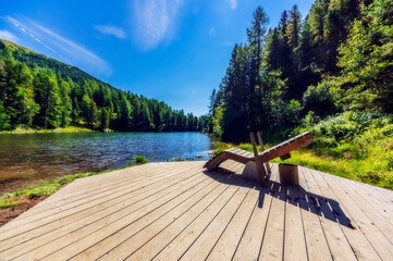 Deck chair on jetty by lake at Turracher Hoehe, Gurktal Alps, Austria