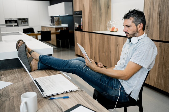 Mature male freelancer holding digital tablet while sitting with feet up on desk at office