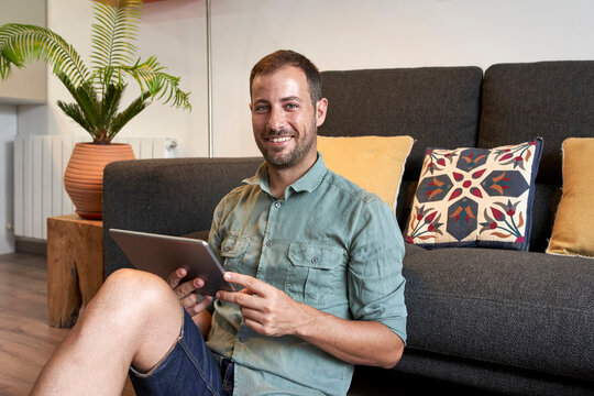 Smiling man sitting on floor with digital tablet against sofa in living room at home