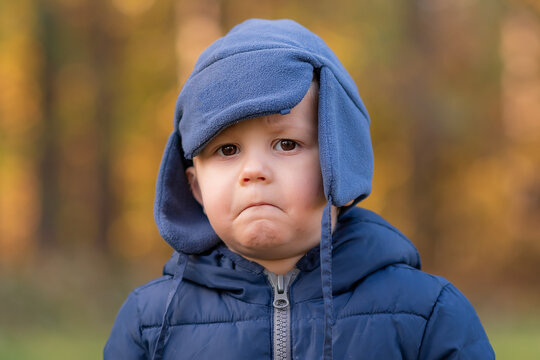 Sad boy is posing on an autumn day. Boy and beautiful bokeh