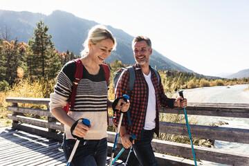 Austria, Alps, happy couple on a hiking trip crossing a bridge Fotobehang