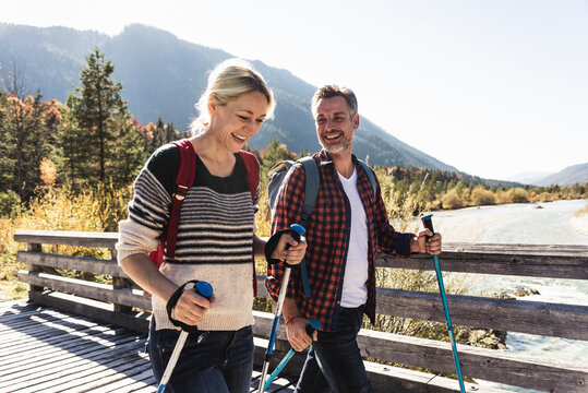 Austria, Alps, happy couple on a hiking trip crossing a bridge
