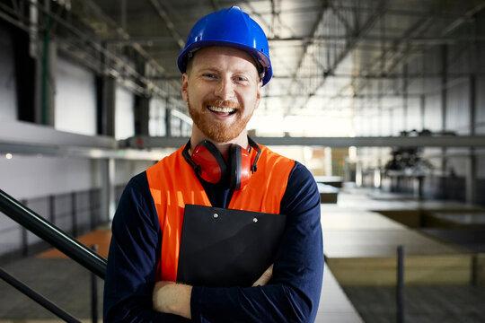 Portrait of happy worker in factory warehouse