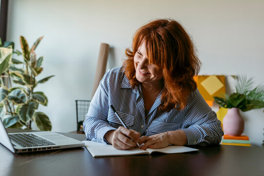 Smiling woman writing book while sitting by table at home