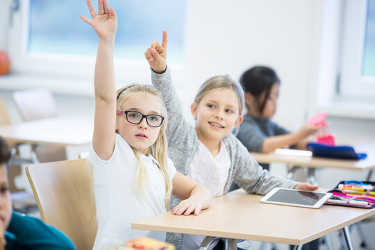 Schoolgirls with tablet raising their hands in class