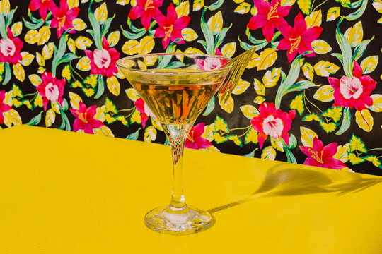 Glass of Cocktail liquor kept on yellow table in studio