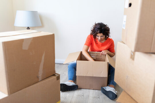 Woman moving into new looking into cardboard box