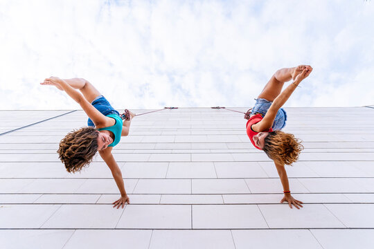 Aerial dancers touching toes while hanging on window