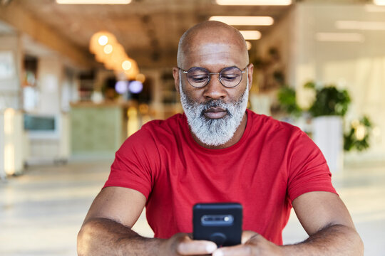 Mature man in red t-shirt using smart phone while sitting at rooftop