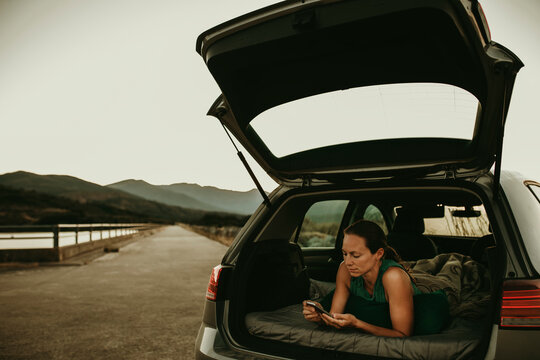 Woman using smart phone while lying in car trunk against clear sky