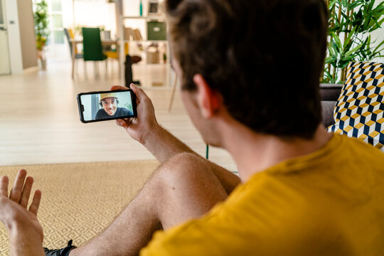 Personal trainer giving fitness advice on video call while sitting at home