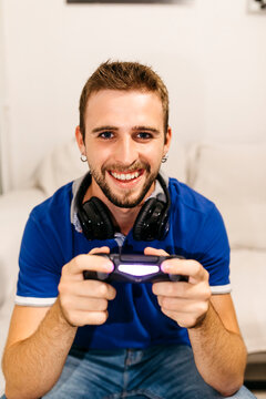 Smiling handsome young man playing video game at home