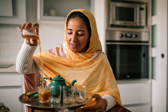 Young woman pouring tea in cup at home