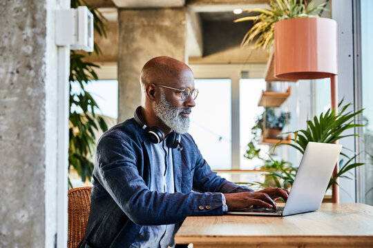 Mature man doing freelance work while sitting at home