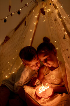 Cute sibling holding christmas light while sitting in room