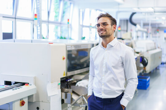 Smiling young male technician standing with hands in pockets at illuminated factory