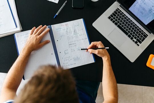 Male student solving mathematical equations in workbook while sitting at table