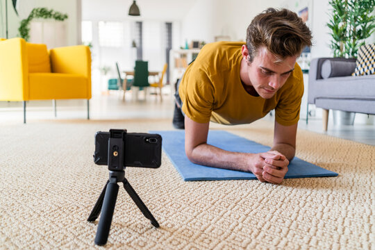 Fitness trainer with tripod doing plank on exercise mat at home