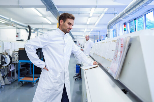 Young male technician in lab coat looking at reports on machinery