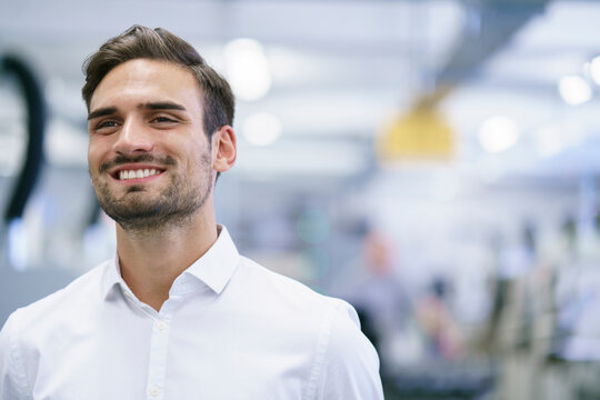 Smiling young male professional looking away while standing at illuminated factory