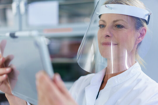 Mature female scientist wearing protective face shield while using digital tablet at laboratory