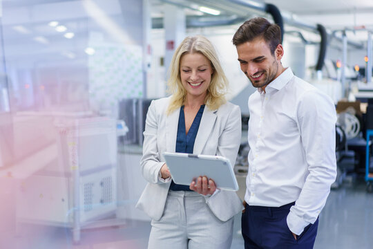 Smiling blond businesswoman discussing over digital tablet with young male colleague at factory