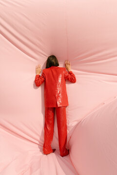 woman wearing red shiny suit playing with a huge fabric