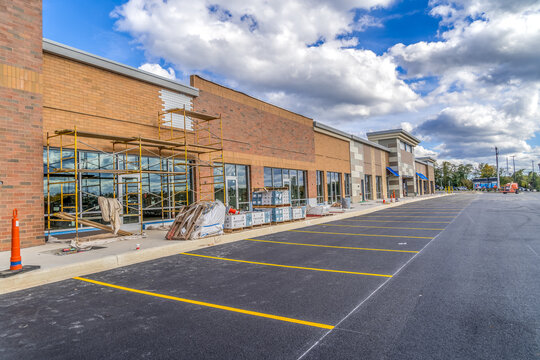 Refurbished strip mall commercial real estate property under construction in Maryland covered with orange, red brick veneer and scaffolding