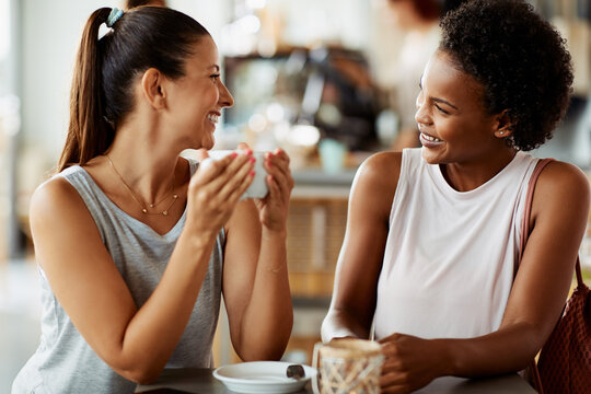 Two friends laughing over coffee in a cafe