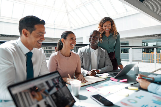 Laughing group of diverse businesspeople working in an office building