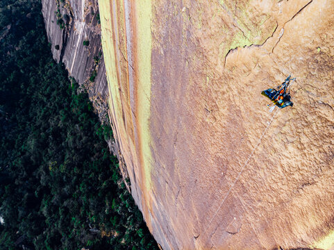 High angle view of rock climber sitting on portaledge in stunning big wall