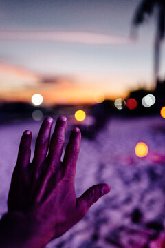 Hand of a man in a beach at night with lights