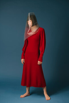 woman with red dress covering her face with a transparent plastic sheet