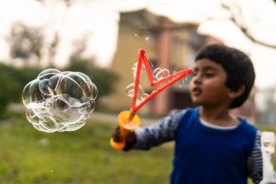 Cute little girl enjoying blowing soap bubbles at outdoors