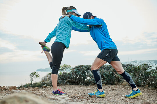 Fit couple helping each other stretch before a trail run