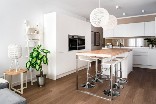 Modern dining room with two pendant lamps over dining table, chairs and oven