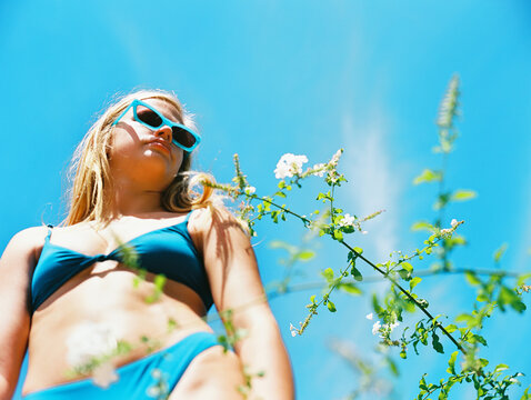 Blonde woman teenager in blue bathing suit on sunny day with sunglasses
