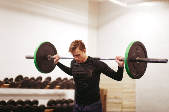 Young man working out with heavy weights at the gym