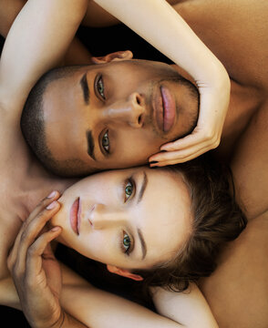 Dark-skinned man and light-skinned girl cuddling on a dark background