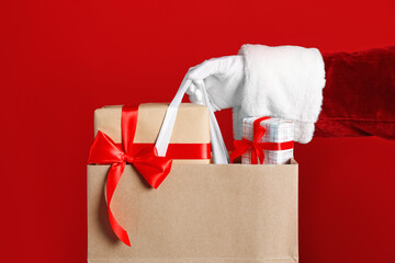 Santa holding paper bag with gift boxes on red background, closeup