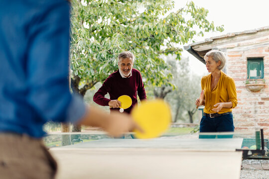 Parents playing table tennis with son