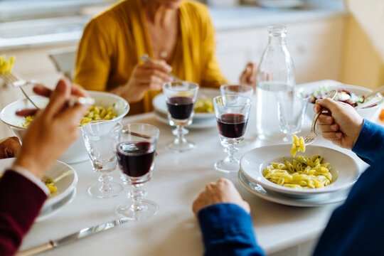 Unrecognizable family having pasta and wine for dinner