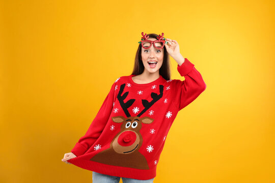 Surprised young woman in Christmas sweater and party glasses on yellow background