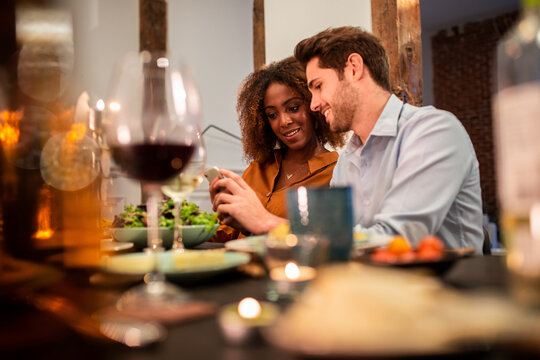 Cheerful young couple using smartphone at dinner