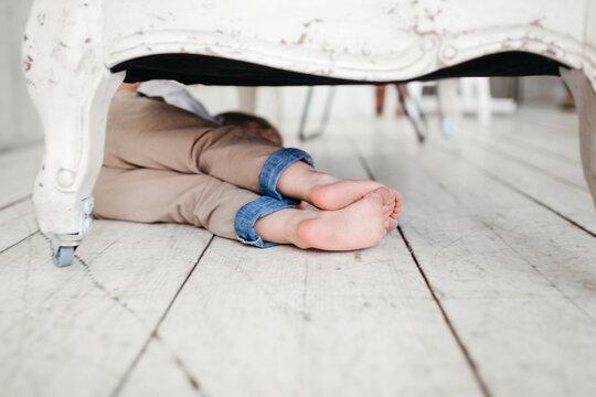 A little boy is hiding under the sofa.
