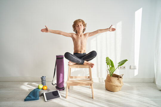 Kid with closed eyes and raising hands sitting crossed legged on top of a chair while doing yoga at home