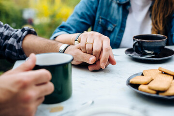 Crop couple holding hands on table having teatime